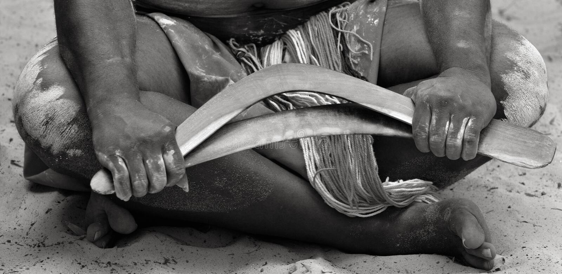 As mãos do homem aborígene do worrior de Yugambeh guardam Bumerangues fotos de stock royalty free