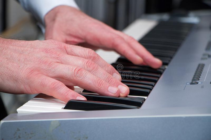 As mãos do homem bonito nas chaves do sintetizador fotos de stock royalty free