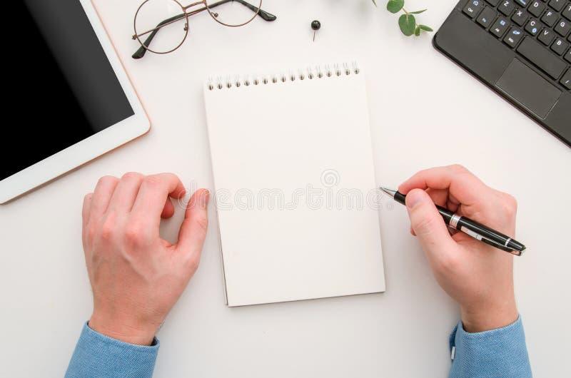 As mãos do homem da vista superior com o bloco de notas na mesa de escritório Local de trabalho com caderno, tabuleta, vidros, pe imagem de stock