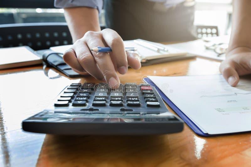 As mãos do homem de negócios usando a calculadora e os dados financeiros que analisam na mesa de madeira no escritório fotografia de stock
