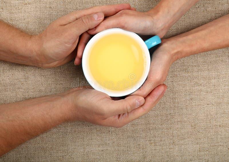 As mãos do homem e da mulher guardam o copo de chá verde completo fotos de stock
