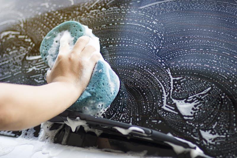 As mãos do homem guardam com o carro azul da lavagem da esponja imagem de stock royalty free