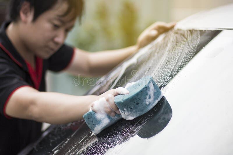 As mãos do homem guardam com o carro azul da lavagem da esponja imagens de stock