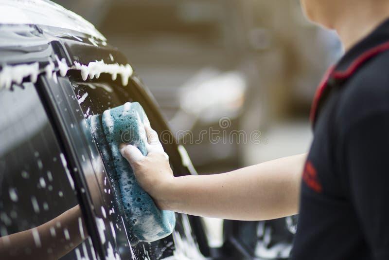 As mãos do homem guardam com o carro azul da lavagem da esponja foto de stock
