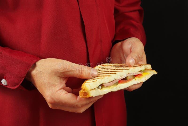 As mãos do homem na camisa vermelha estão guardando um sanduíche em upHands pretos de um fim do fundo do homem em uma camisa verm foto de stock royalty free