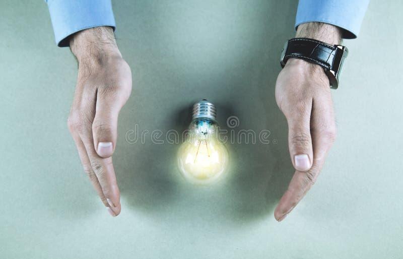 As mãos do homem protegem a ampola Energia elétrica de salvamento imagens de stock royalty free