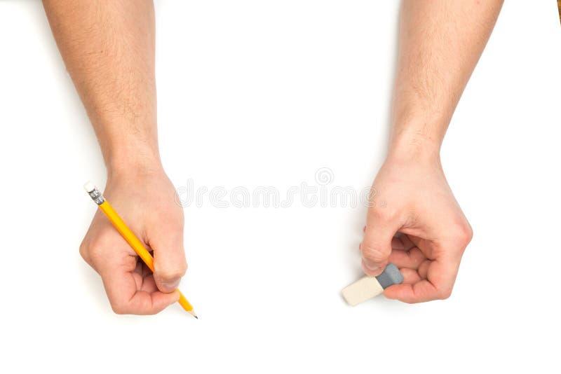 As mãos do homem que escrevem com lápis e eracer de madeira no fundo branco isolado com lugar do texto fotos de stock