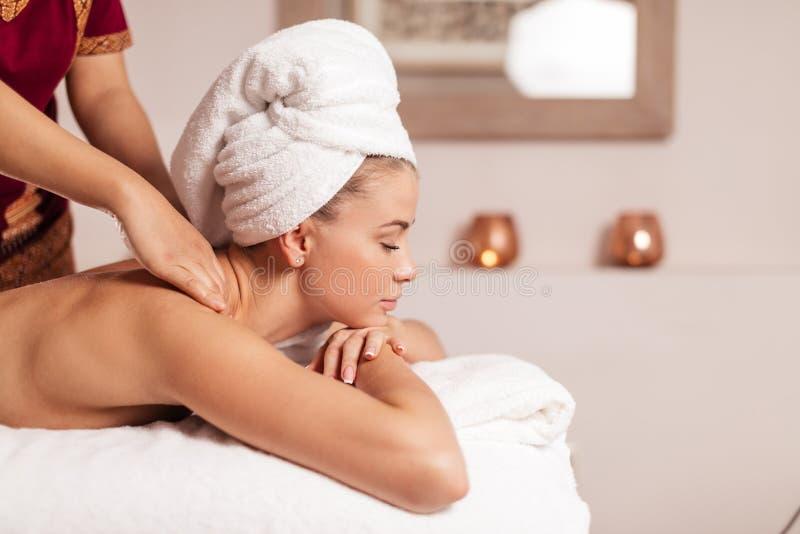 As mãos do homem que fazem massagens os ombros do cliente fotos de stock