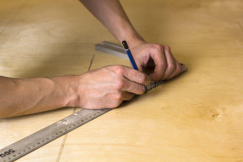 As mãos do homem que marcam a medida na placa da madeira compensada com um lápis e na régua fotografia de stock royalty free