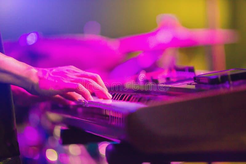 As mãos do músico que jogam o teclado em um espetáculo ao vivo na fase com o instrumento musical obscuro fotografia de stock