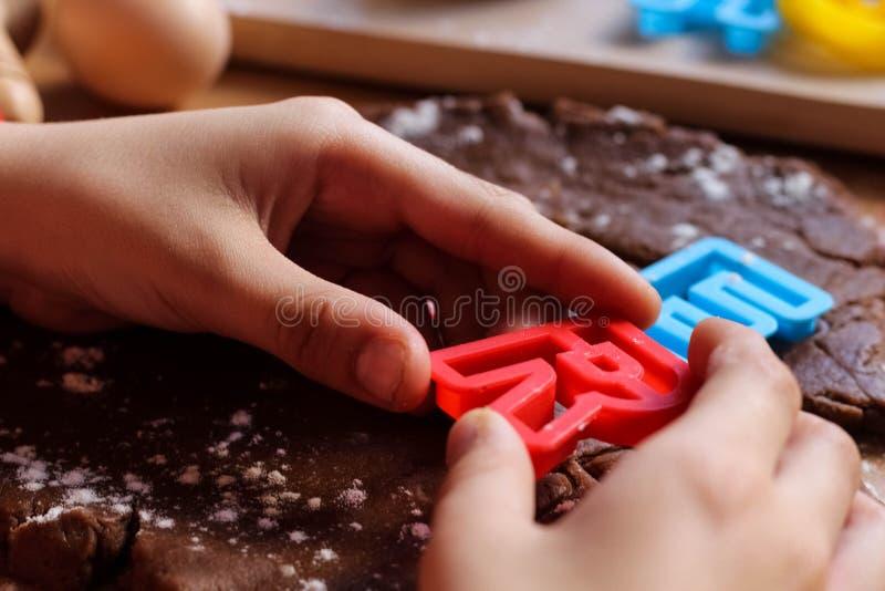 As m?os do menino dos jovens cortaram cookies da massa crua do chocolate em uma tabela de madeira com letras coloridas Cozinhando fotos de stock royalty free