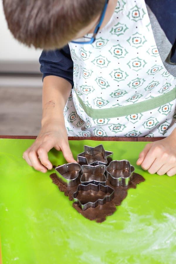 As mãos do menino que espremem formas dos moldes de metal de um bolo colocado em uma placa verde da pastelaria do silicone Ativid fotos de stock royalty free