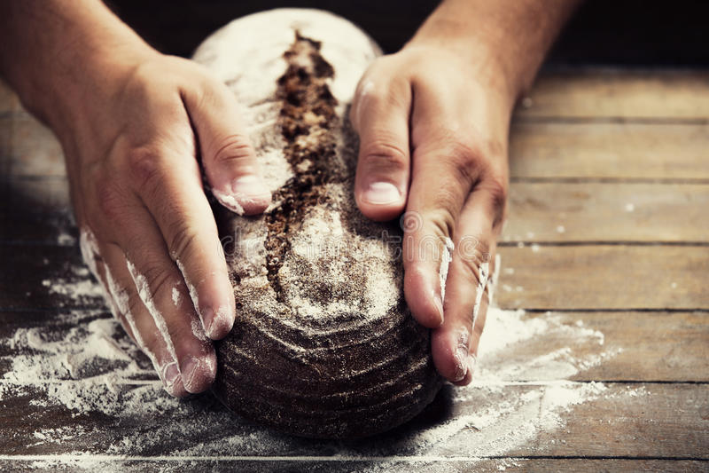 As mãos do padeiro com um pão fotografia de stock