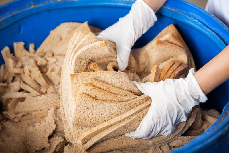As mãos do padeiro que rejeitam o desperdício do pão no escaninho de lixo fotografia de stock