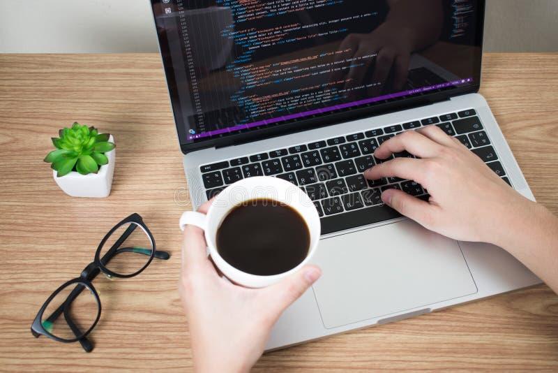 As m?os do programador est?o analisando alguns sistemas e informa??o no tela de computador ao beber o caf? na mesa fotos de stock royalty free