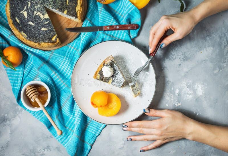 As mãos do ` s da mulher cortaram o bolo de queijo delicioso da semente de papoila na tabela concreta imagens de stock royalty free