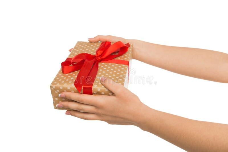 As mãos do ` s da mulher dão a caixa atual isolada no branco imagem de stock