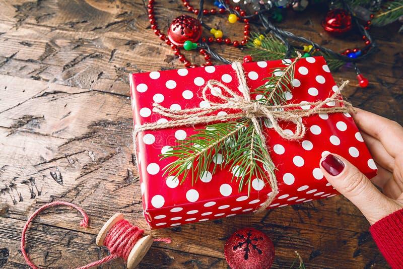 As mãos do ` s da mulher dão o presente do Natal imagens de stock