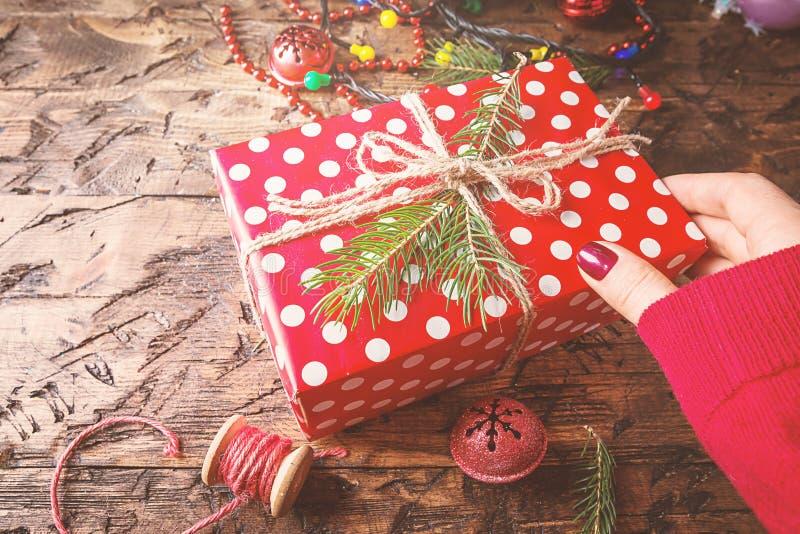 As mãos do ` s da mulher dão o presente do Natal imagem de stock royalty free