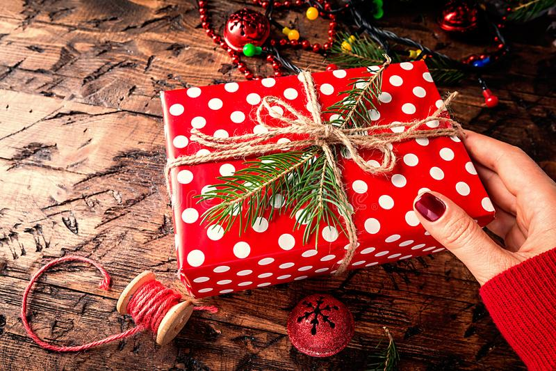 As mãos do ` s da mulher dão o presente do Natal foto de stock