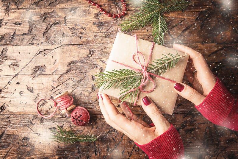 As mãos do ` s da mulher dão o presente do Natal imagem de stock
