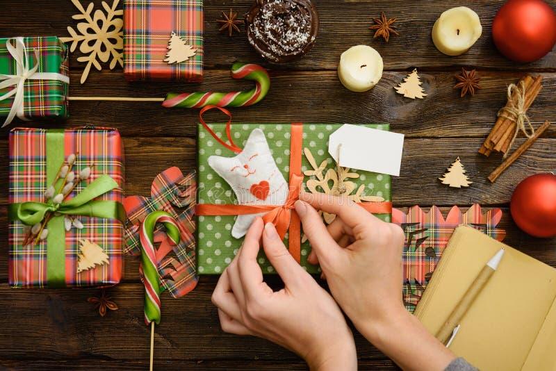 As mãos do ` s da mulher envolvem o presente feito a mão do Natal no papel foto de stock royalty free