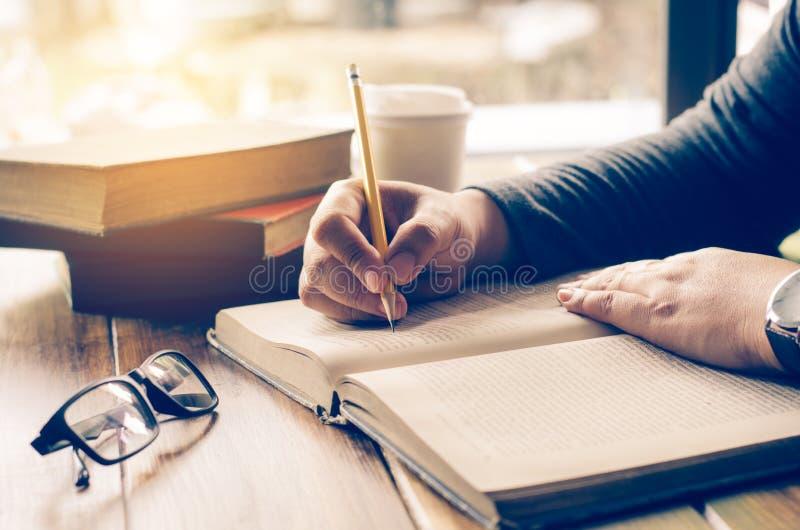 As mãos do ` s da mulher estão escrevendo notas em um caderno imagens de stock royalty free