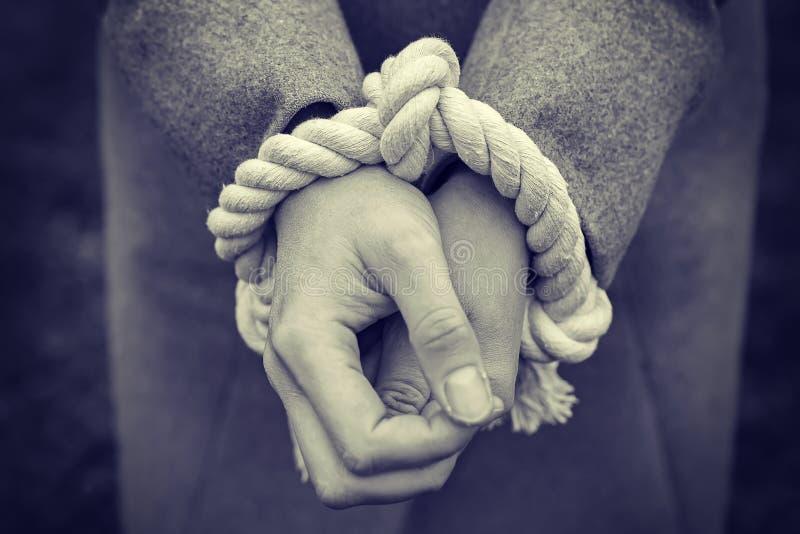 As mãos do ` s da mulher são amarradas com corda O conceito da liberdade e de direitos humanos Violência e problemas sociais imagem de stock royalty free