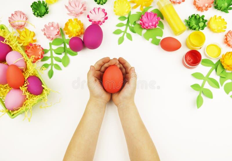 As mãos do ` s das crianças guardam um ovo da páscoa Páscoa Mola Faculdade criadora do ` s das crianças foto de stock