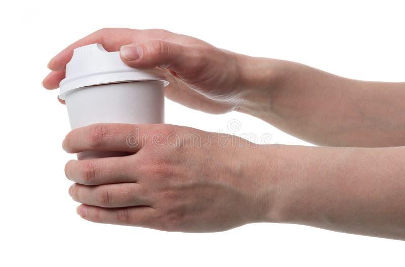As mãos do ` s das mulheres abrem a tampa do copo descartável para bebidas quentes, isolado no branco foto de stock royalty free