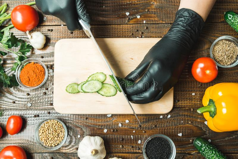 As mãos do ` s das mulheres cortaram um pepino, perto dos tomates, da paprika e do alho imagens de stock royalty free