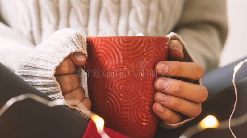 As mãos do ` s das mulheres na camiseta estão guardando o copo do café, do chocolate ou do chá quente Conforto do inverno do conc foto de stock royalty free