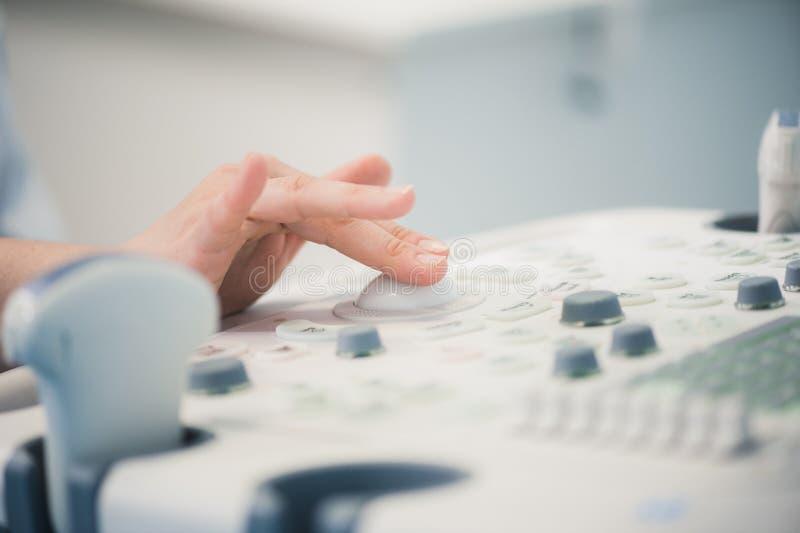 As mãos do ` s do doutor da jovem mulher fecham-se acima da preparação para uma varredura do dispositivo do ultrassom fotografia de stock royalty free