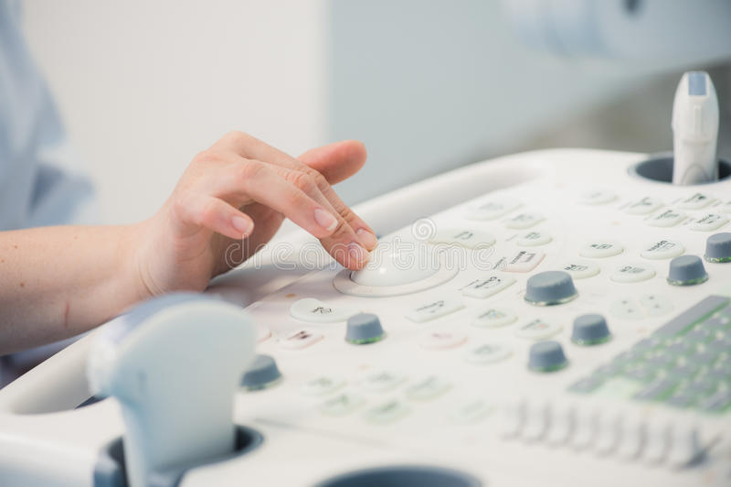 As mãos do ` s do doutor da jovem mulher fecham-se acima da preparação para uma varredura do dispositivo do ultrassom imagem de stock