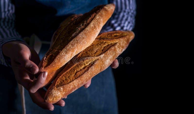 As mãos do ` s do padeiro guardam o pão fresco sobre o fundo escuro fotos de stock