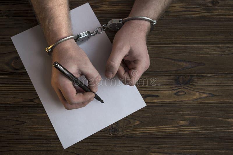 As mãos do ` s dos homens com algemas enchem o registro da polícia, confissão fotos de stock royalty free