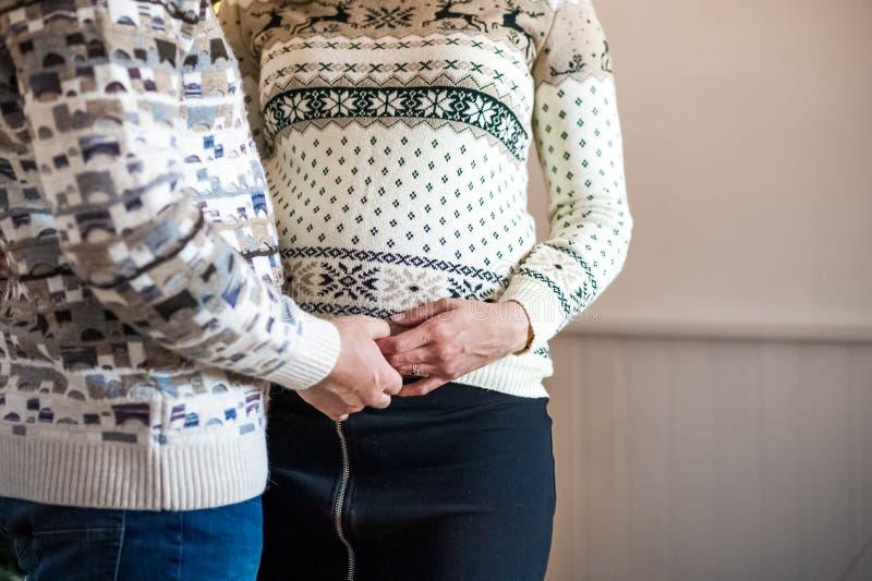 As mãos do ` s dos homens e das mulheres guardam a barriga grávida imagem de stock