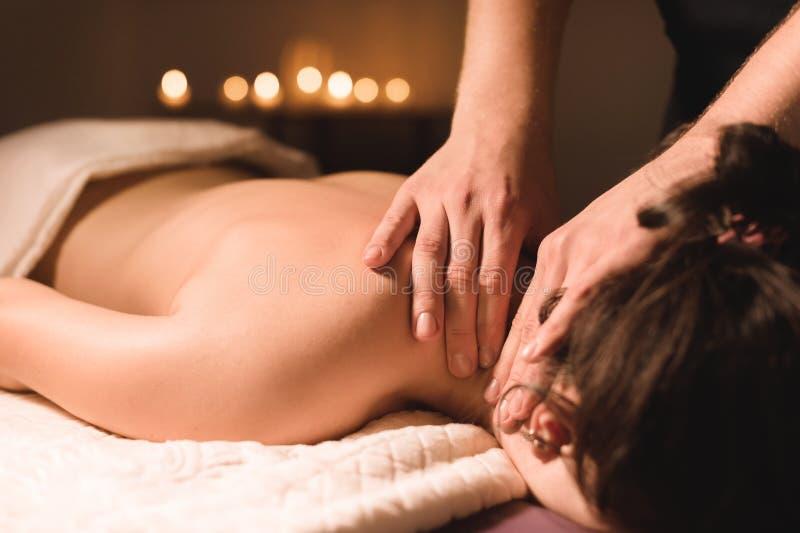 As mãos do ` s dos homens fazem uma massagem terapêutica do pescoço para uma menina que encontra-se em um sofá da massagem em uns imagens de stock royalty free
