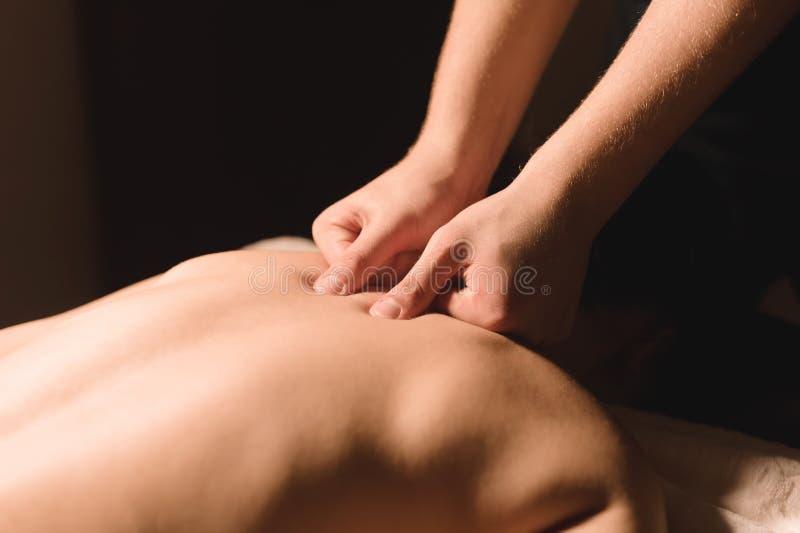 As mãos do ` s dos homens fazem uma massagem terapêutica do pescoço para uma menina que encontra-se em um sofá da massagem em uns foto de stock royalty free