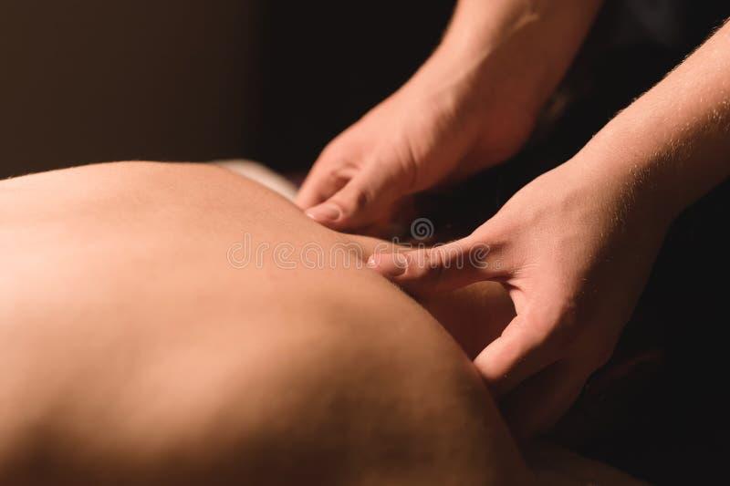 As mãos do ` s dos homens fazem uma massagem terapêutica do pescoço para uma menina que encontra-se em um sofá da massagem em uns imagem de stock