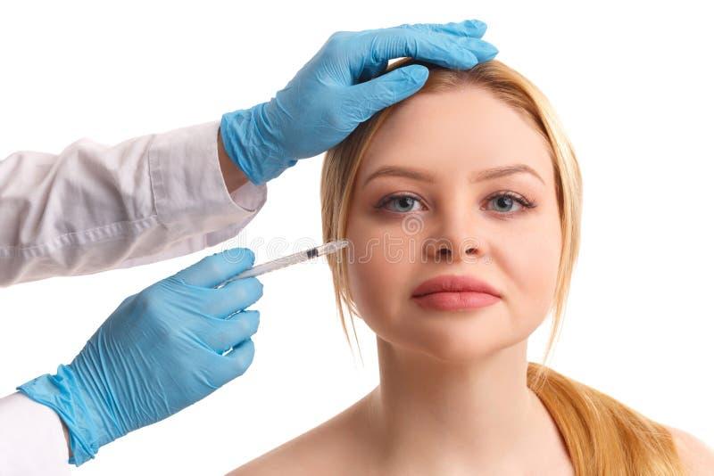 As mãos do ` s do doutor injetam Botox na mulher da cara Isolado fotos de stock