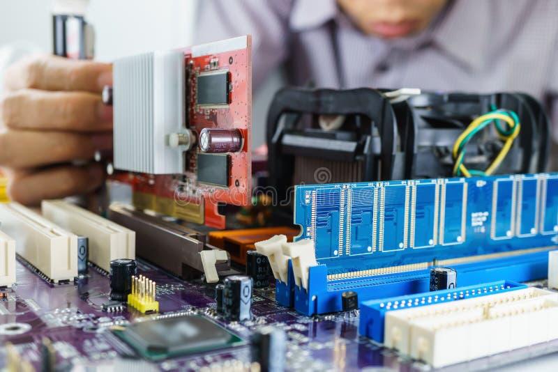 As mãos do técnico que instalam o cartão de VGA fotos de stock royalty free