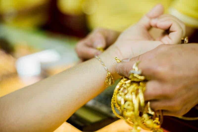 As mãos dos clientes e dos salespeople das mulheres que tentam vestir braceletes de vários tipos de joia do ouro imagens de stock royalty free
