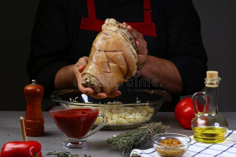 As mãos dos homens, close-up, guardando a junta cortada da carne de porco com o chucrute, cozinhado para o conceito de cozimento  fotos de stock royalty free