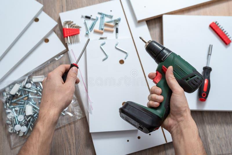 As mãos dos homens com as ferramentas com elementos da mobília no assoalho fotografia de stock royalty free