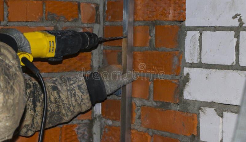 As mãos dos homens nas luvas de trabalho, furo de broca nos perfis de aço, para instalar o quadro sob a isolação fotografia de stock