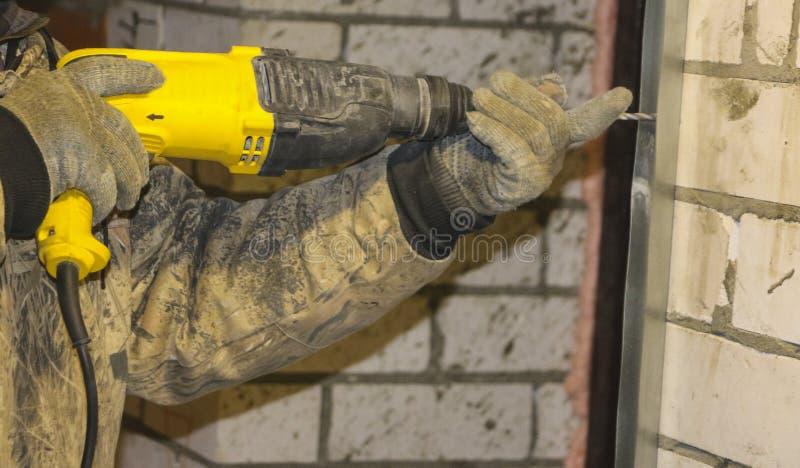 As mãos dos homens nas luvas de trabalho, furo de broca nos perfis de aço, para instalar o quadro sob a isolação foto de stock