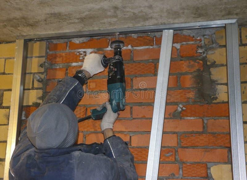 As mãos dos homens nas luvas de trabalho, furo de broca nos perfis de aço, para instalar o quadro sob a isolação imagens de stock