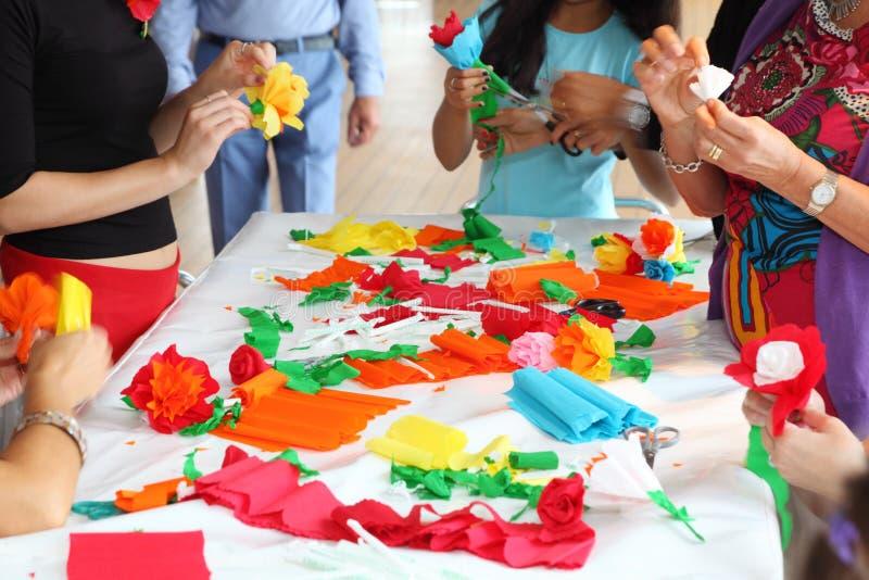 As mãos dos povos fazem flores artificiais foto de stock