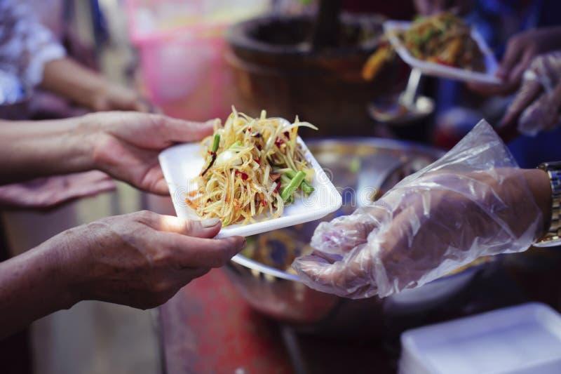 As mãos dos refugiados foram ajudadas pelo alimento da caridade para aliviar a fome: Conceitos de alimentação: A mão ofereceu doa foto de stock royalty free